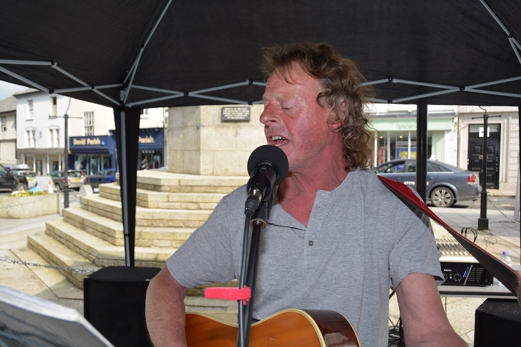 A modern-day troubadour serenading the Town Square on Saturday